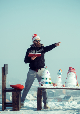 Man santa pointing finger on winter day. Hipster in glasses with book on blue sky. Snowmen and snow xmas tree on wooden table. Christmas and new year holidays celebration. Learning and fun concept.