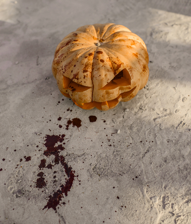 Halloween pumpkin bleeding on cement background. Jack o lantern with red blood and bloodstains on ground. Squash with carved smiley face. Autumn tradition and symbol. Holiday celebration concept Banco de Imagens
