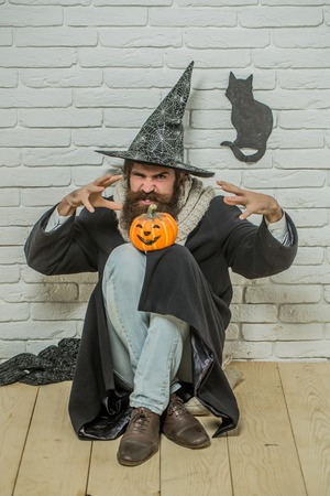 Halloween bad luck. Man in witch hat doing magic on floor. Evil spell concept. Angry hipster with pumpkin and black cat symbol on wall. Autumn holidays celebration.