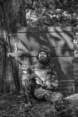 Young soldier hipster with tired bearded face in military ammunition armed with rifle in hands sitting leaned on wooden green shield in forest