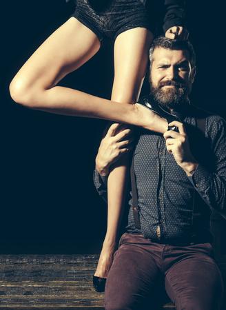 Liefde en relaties, domineren. Mens in overhemd op zwarte achtergrond, matriarchie wordt geïsoleerd die. Benen van vrouw in schoenen bij de mens met baard. Jongen aan tafel met vrouwelijke benen. Romantiek en verliefd.
