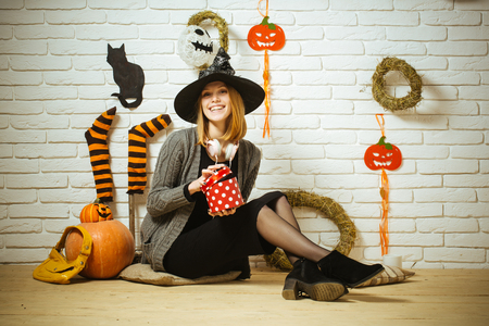 Halloween woman smiling with gift box and bag. Surprise and present concept. Girl in witch hat sitting on floor. Happy holiday celebration. Pumpkins, stockings, wreaths, cat, mummy decorations on wall
