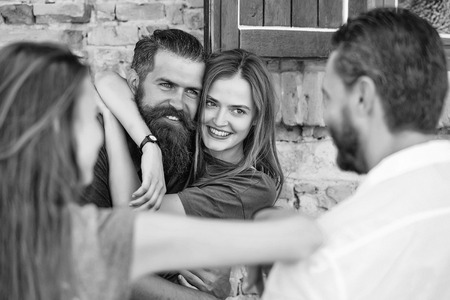 Couple of handsome bearded man with long beard and stylish hair and blonde pretty cute sexy woman or girl embracing and smiling to they friends on summer sunny day on stony wall background Imagens