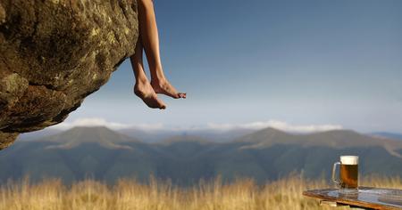 나무 테이블 및 푸른 하늘에 산 풍경에 돌에 매달려 맨발로 여성 다리에 유리 낯 짝에 맥주. 행복과 다과 개념입니다. 여행과 방랑벽