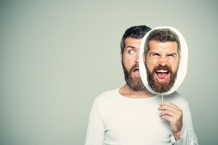Guy or bearded man on grey background. Feeling and emotions. Hipster with surprised and angry face hold portrait nameplate. Man with long beard and mustache. Barber fashion and beauty., copy space