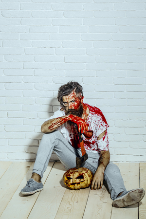 Halloween man sitting with pumpkin and axe on wooden floor. Bearded hipster with red blood splatters. Maniac and bloody jack o lantern. Psychopath bleeding in torn tshirt. Halloween holiday concept.