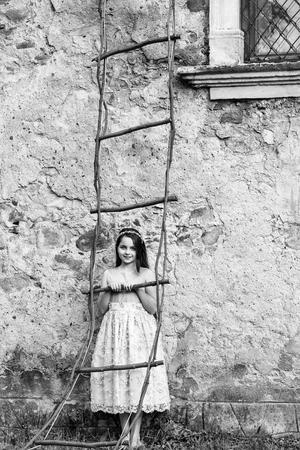 Belle petite fille en robe et couronne sur des escaliers de pierre de fée en bois près du mur de construction avec fenêtre en plein air Banque d'images - 87719316