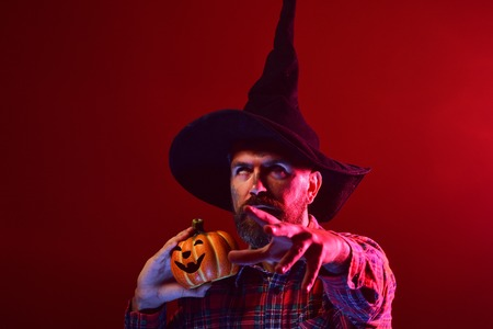 Halloween trick or treat. Hipster in wizard hat holding pumpkin on red background. Man rolling eyes with jack o lantern. Autumn holiday celebration. Mystery and magic concept. Stock Photo