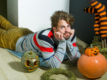 Halloween man with messy hair lying on floor. Pumpkins, striped stockings and wreath. Autumn and harvest season. Holidays celebration concept. Trick or treat.
