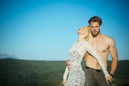 Man or macho with torso in jeans. Woman or girl with long blond hair in lace dress. Couple in love on blue sky. Fashion and beauty. Relationship, heterosexual and lifestyle concept, copy space Stock Photo - 87719323