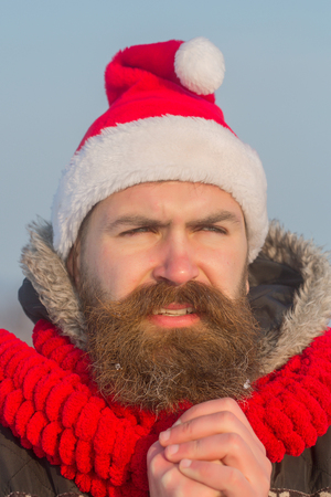 New year guy on blue sky. Xmas party celebration. Winter happy holiday and vacation. Christmas man with long beard and mustache on face. Santa claus hipster in red hat and scarf. Stock Photo