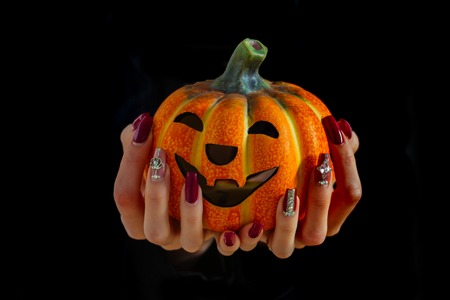 Halloween jack o lantern in female hands isolated on black background. Pumpkin and manicure with gems and sequins. Nail art concept. Holiday and party celebration. Autumn and harvest season.