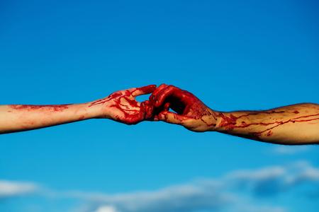 ゾンビの手が男性と女性の戦争の兵士の男と女の子または血の傷と青い空を背景には、皮膚上の赤い血の女性 写真素材