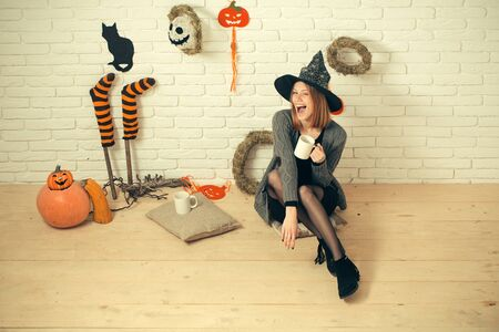 Halloween woman in witch hat winking with cups. Happy holiday celebration concept. Girl sitting on wooden floor. Coffee or tea break. Pumpkins, wreaths, mummy symbols and decorations on brick wall. Stock Photo - 87567603