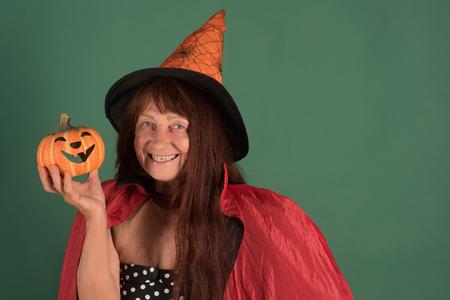 Halloween vakantie feest concept. Vrouw die met pompoen op groene achtergrond glimlacht. Snoep of je leven. Kwaadaardige betovering en magie. Hogere dame met lang rood haar in heksenhoed, exemplaarruimte