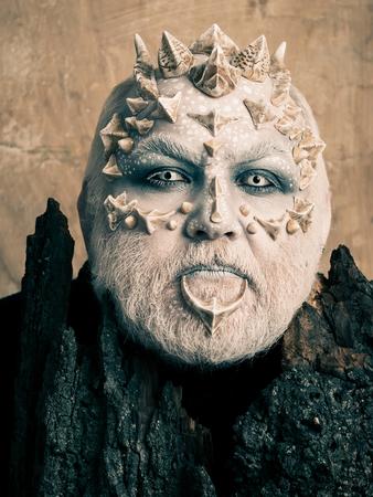 트리 정신 및 판타지 개념입니다. 베이지 색 벽에 오래 된 나무 껍질 뒤에 사제. 날카로운 가시와 사마귀가있는 괴물. 드래곤 피부와 수염 난 얼굴을 가 스톡 콘텐츠