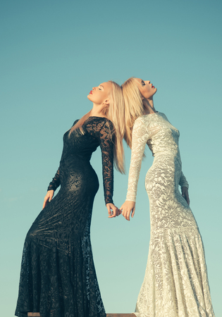 Fashion and beauty. Women wearing black and white dresses. Choice, decision and future. Opposites and contrasts concept. Two girls with long blond hair posing on blue sky. Фото со стока