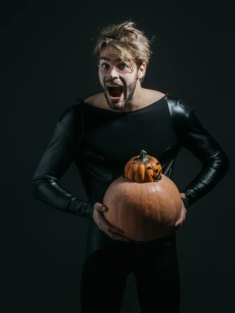 Halloween macho excited with open mouth in black costume. Man holding two pumpkins on dark background. Autumn and harvest season. Holidays celebration concept. Trick or treat. Stock fotó