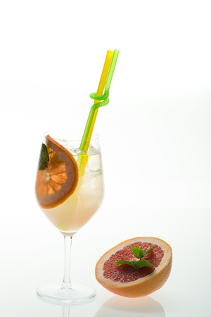 Cocktail isolated on white background. Party and summer vacation. Alcoholic beverage and orange at restaurant. Drink and food. Fruit slice of grapefruit in cocktail glass at bar. Stock Photo