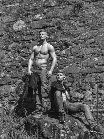 男性裸胸若いポーズ ツイン兄弟ジーンズ壁画の背景に屋外でセクシーなモデル 写真素材