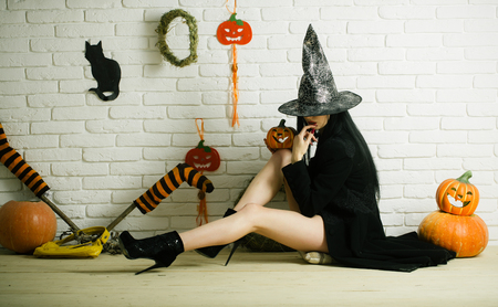 Halloween evil spell and magic. Girl with pumpkins, striped stockings, black cat on wall. Woman in witch hat and coat sitting on floor. Tradition and traditional symbols. Holiday celebration concept. Stock Photo