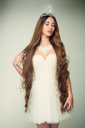 Girl has fashionable makeup and healthy hair on grey background. Beauty salon and wedding fashion. Hairdresser and cosmetics. Haircare and prom queen. Woman with long hair white dress and crown. Stock Photo