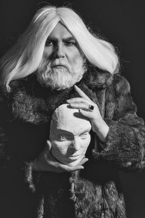 暗い背景にリングと手に白い彫刻の頭を保持毛皮のコートに長いひげを持つ古いドルイドの髭の男 写真素材 - 87848857