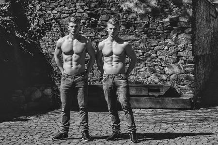 セクシーな若いスポーツマン深刻な双子兄弟壁画の背景にシャツにジーンズでポーズ