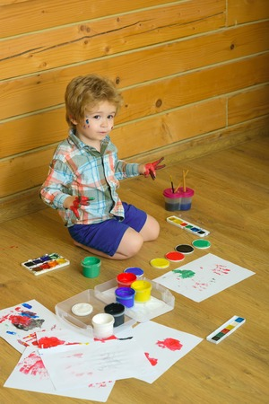 paintings: Kid learning and playing. Boy painter painting on wooden floor. Arts and crafts. Imagination, creativity and freedom concept. Child with colored hands, gouache paints and drawings. Stock Photo