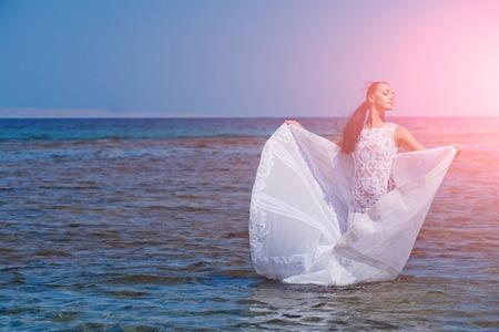 Mariée le jour d'été ensoleillé sur l'eau bleue. Concept de voyage de lune de miel. Mode et beauté. Femme posant sur la plage de la mer Fille en robe de mariée blanche. Banque d'images - 87567690