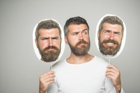 ファッションと美容理容室します。悲しい顔で流行に敏感な肖像画銘板を保持します。感覚や感情。長いひげと口ひげを持つ男。男や背景が灰色の