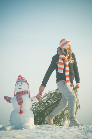 Kerel en sneeuwbeeld die hoeden en sjaals dragen. Mens en sneeuwman die op blauwe hemel lopen. Kerstmis en Nieuwjaar. Hipster slepende Kerstmisboom op sneeuw de winterweg. Vakantie feest concept. Stockfoto