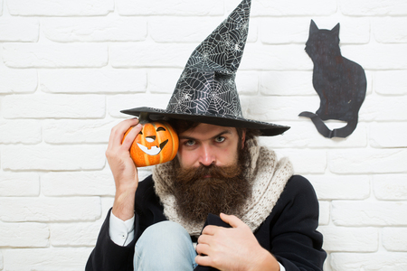 Halloween hipster with pumpkin and black cat symbol on wall. Man in witch hat sitting on floor. Bad luck concept. Autumn holidays celebration. Evil spell and magic.