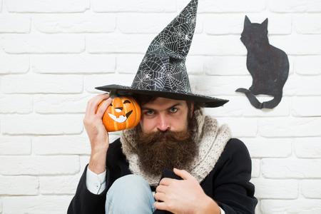 Hipster de Halloween con calabaza y símbolo de gato negro en la pared. Hombre con sombrero de bruja sentado en el piso. Concepto de mala suerte. Celebración de vacaciones de otoño. Mal hechizo y magia Foto de archivo - 87567713