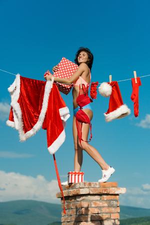 Kerst meisje met happy hold preset vak op kerstmuts, rode jas, sok, beha, shorts en ribbelst op schoorsteen zonnige zomer buiten op blauwe hemelachtergrond