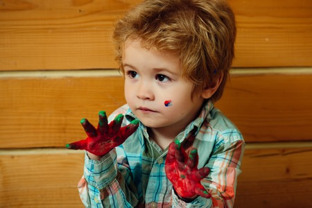 paintings: Boy artist sitting on wooden wall. Child with hands colored with paint. Arts and crafts. Imagination, creativity and freedom. Handprint painting concept.