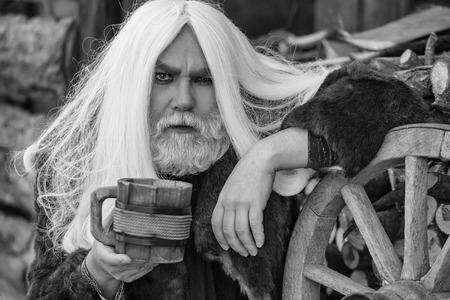 灰色の長い髪と屋外ホイール付近の手の木製マグカップと毛皮のコートでひげドルイド古いひげを生やした男