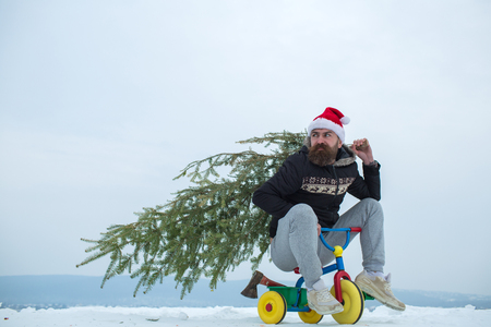 Man riding tricycle on snowy landscape. Cyclist in santa hat and sporty wear. Holiday celebration concept. Christmas and new year. Hipster carrying xmas tree and axe on white snow. Stock Photo