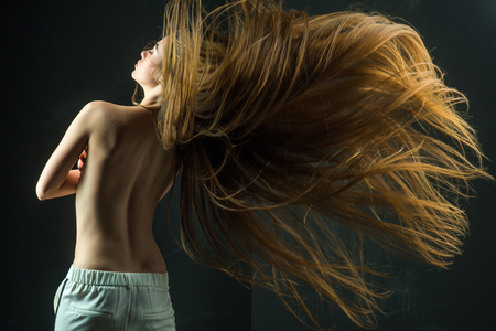 woman with long healthy hair and naked back on black background, hairdresser and beauty salon