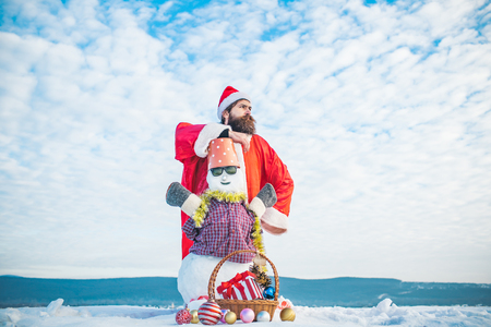 Snowman in glasses and bucket on head. Man in santa hat looking into distance. Winter holidays concept. Christmas basket and new year balls on snow. Hipster standing in red xmas costume. 版權商用圖片 - 88476216