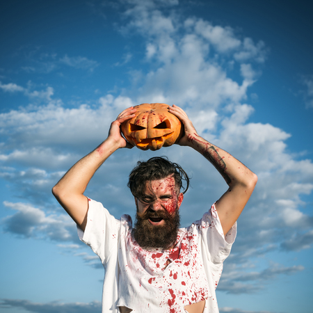 Halloween soldier in bloody torn tshirt with jack o lantern. Hipster with red blood shouting angry. Aggression, war concept. Autumn holiday celebration. Man holding pumpkin overhead on cloudy blue sky Stock Photo