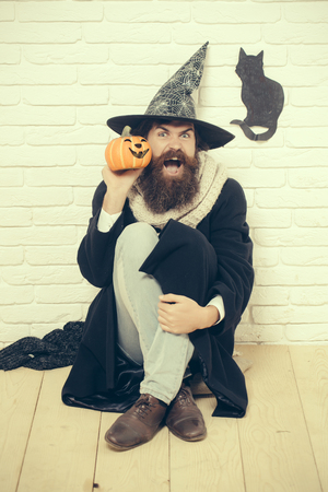 Halloween bad luck concept. Man in witch hat sitting on floor. Autumn holidays celebration. Hipster shouting with pumpkin and black cat symbol on wall. Evil spell and magic.
