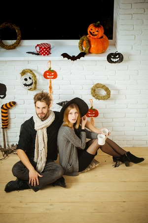 Halloween couple in love with cups sitting under window. Macho or man wearing in scarf. Woman or girl in witch hat. Festive and homely atmosphere. Holiday celebration concept.