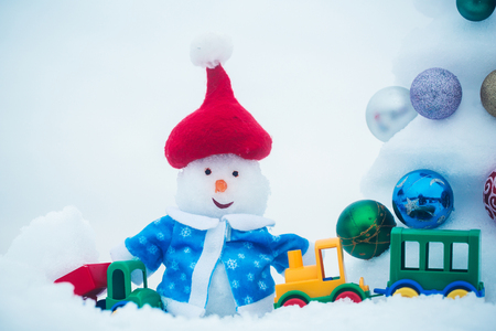 Snow sculpture with toy car and train. Snowman in red hat and blue coat on white background. xmas decorations and balls. Christmas and new year. Holidays celebration concept