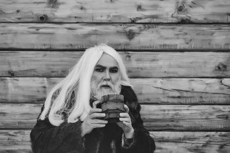 ドルイド灰色の長い髪と手ウッドの背景に屋外の木製マグカップの深刻な顔に髭を持つ老人