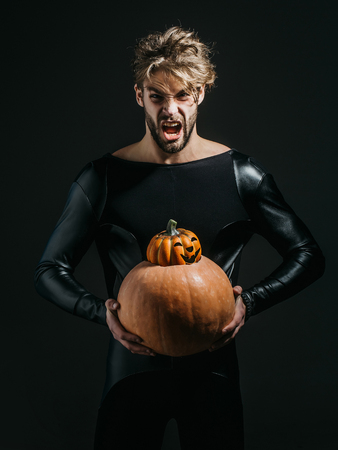 Halloween macho with angry face in black costume. Trick or treat. Man holding two pumpkins on dark background. Autumn and harvest season. Holidays celebration concept.