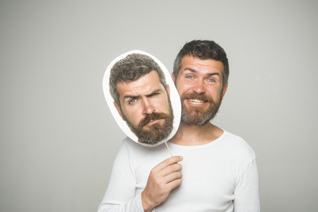 Barber fashion and beauty. Feeling and emotions. Man with long beard and mustache. Hipster with sad and happy face hold portrait nameplate. Guy or bearded man on grey background.