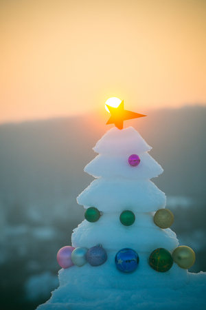 Decorations and ornaments. xmas and new year celebration. Winter holidays concept. Christmas tree with baubles on sunset sky. Snow sculpture with red star on natural background.