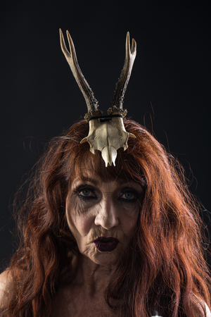 Halloween old lady with candle and antler. Halloween holiday celebration. woman in black with long red hair and makeup. traditional party. old woman on black background. Stock Photo - 87713426