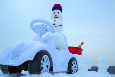 Snowman driving toy car on white sky on winter day on snowy background. Christmas and new year. Holidays celebration concept
